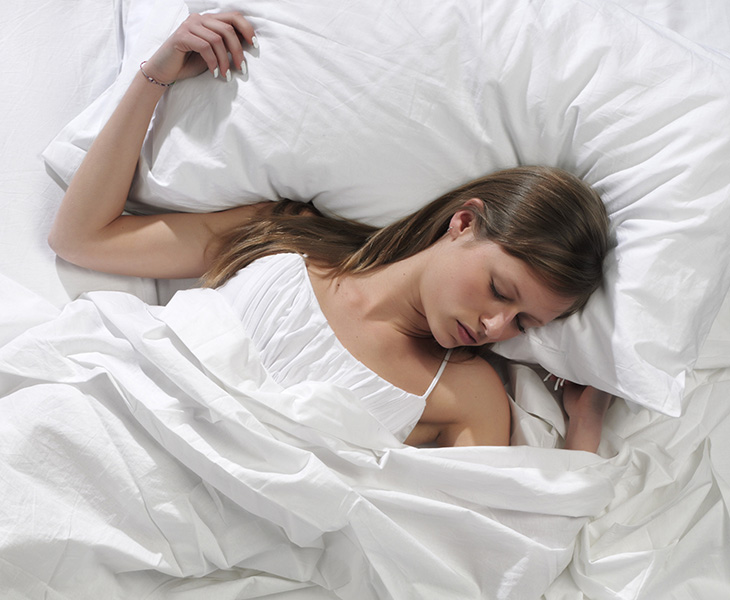 Young blonde woman sleeping in the bed